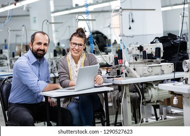 Businessman and adult woman working with computer in factory.