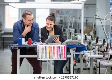 Businessman and adult woman working with digital tablet in factory.