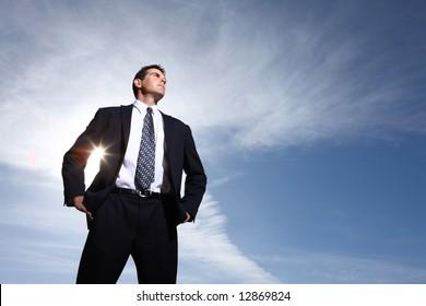 Businessman against cloudy sky