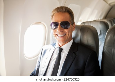 Businessman in airplane. Confident mature businessman sitting at his seat in airplane and smiling