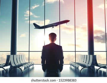 Businessman in airport and looking at airplane flying in sky. Travel and transportation concept