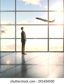 businessman in airport looking to airplane in sky