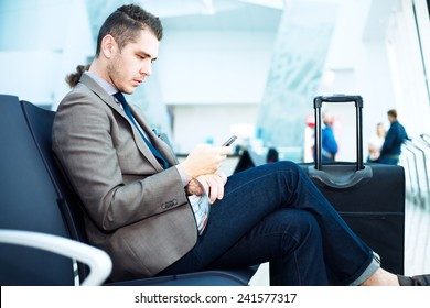 Businessman at airport with smartphone and suitcase checking emails before boarding