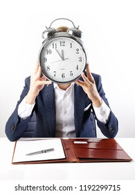 Businessman with alarm clock in front his face, running out of time