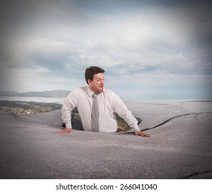 Businessman alone and afraid swallowed by asphalt