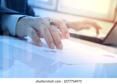 Businessman analysing business investment data with laptop computer notebook and document in the office.