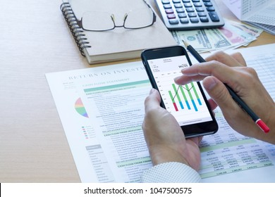 Businessman analysing saving deposit bank account in cash flow statement management with mobile application and left copy space.