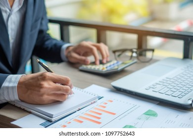 Businessman analysis maketing plan, Accountant calculate financial report, computer with graph chart.  Business, Finance and Accounting concepts