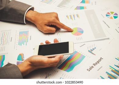 Businessman analysis and making decisions on desk office with business report and his hand holding mobile phone. Marketing and exploring market data for organization, Accounting, budget, price.