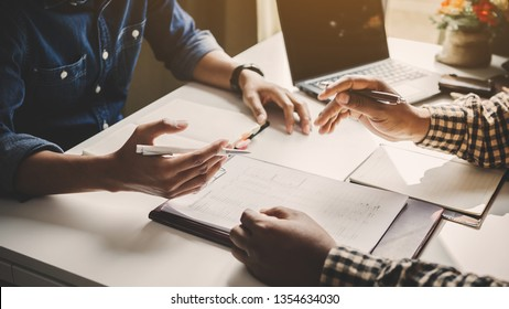 Businessman analyze concept; Young business startup working on market analyst document in graphs and diagram  on notebook; young coworkers crew working with new startup project