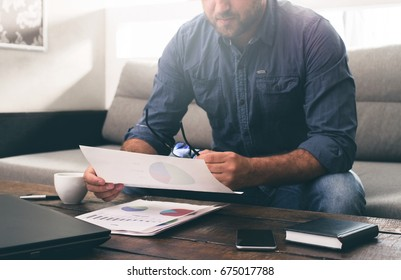 Businessman analyzes the sales report on the sofa at home. Work at home concept