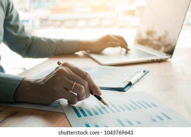 Businessman analyzing annual business report and holding pen and pointing paper chart summary with using laptop at room office desk.