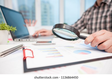 Businessman analyzing business graphs with magnifying glass. With copy space