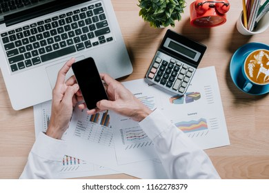Businessman analyzing financial data on smartphone and laptop computer.Top view.Business analysis and strategy concept.