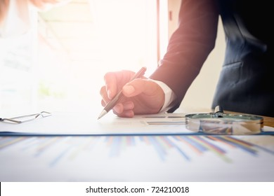 Businessman analyzing graph with chart sheet on office desk