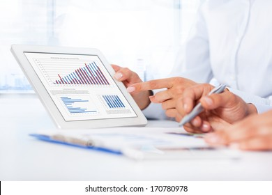 Businessman analyzing graph using digital tablet touch pad, touching hand point finger touch screen, business people group desk office, businesspeople report financial charts