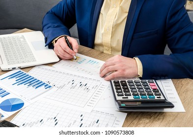Businessman analyzing graphs and diagrams on wooden table