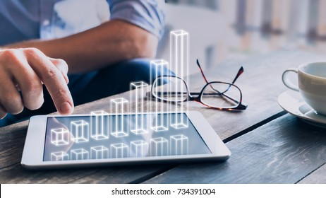Businessman analyzing growing 3D AR chart floating above digital tablet computer screen, showing successful increase in business profit