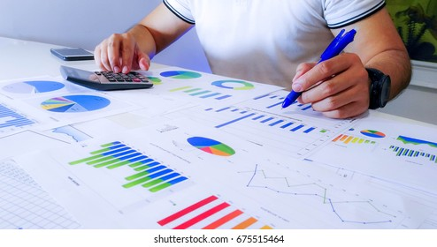 Businessman analyzing income charts and graphs with calculator. Close up.Business financial analysis and strategy concept.