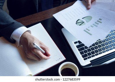 Businessman analyzing investment charts. Accounting. Hands of financial manager taking notes while working