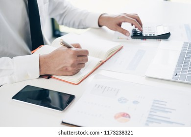 Businessman analyzing investment charts by using his laptop and calculator in modern office, Business and Office concept.