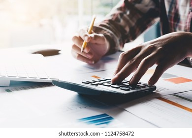 Businessman analyzing investment charts with calculator and laptop computer. Accounting and technology in office,marketting plans.