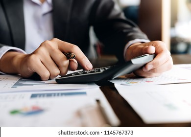 Businessman analyzing investment charts with calculator laptop calculate technology in office,business,Accountant Bookkeeper Concept