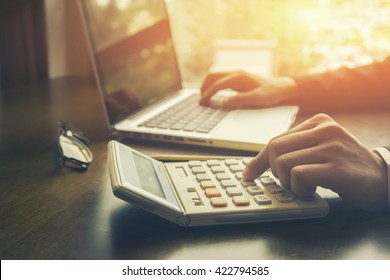 Businessman analyzing investment charts with calculator laptop. Accounting and technology in office.Business people using laptop at office,Analyze plans.selective focus,vintage color