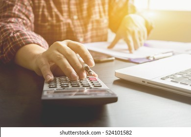 Businessman analyzing investment charts with calculator. Accounting and technology in office while using laptop at office for marketing plans.selective focus,vintage color
