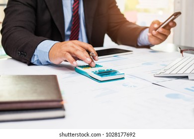 A businessman analyzing investment charts at his workplace and using his calculator and holding a smart phone.