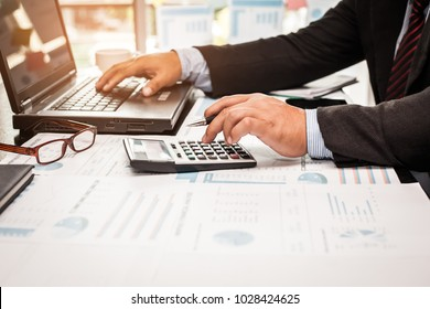 A businessman analyzing investment charts at his workplace and using his laptop and touch calculator.