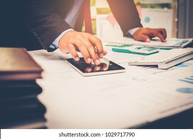 A businessman analyzing investment charts at his workplace and using his tablet ,stock chart , calculator with close up vintage style.