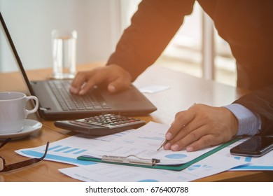 A businessman analyzing investment charts at his workplace and using his laptop ,stock chart , cellphone, close up vintage stlye