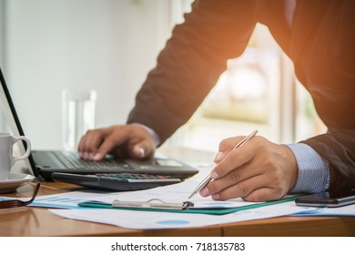 A businessman analyzing investment charts at his workplace and using his laptop ,stock chart , cellphone, close up vintage style.