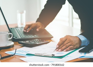 A businessman analyzing investment charts at his workplace. Business concept.