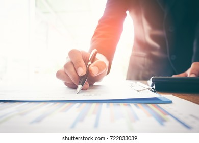 Businessman analyzing investment charts with laptop computer on office desk table.Close up.Financial Report Revenue Statistical Accounting Concept.