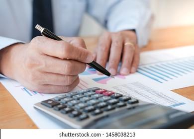 Geschäftsleute analysieren Anlagediagramme und drücken Taster für Taschenrechner über Dokumente. Rechnungslegungskonzept