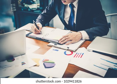 A businessman analyzing investment charts and writing something in his note pad while sitting at the desk in his office. Business concept.