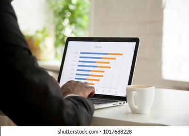Businessman analyzing monthly stats graph on laptop screen, making annual project financial report data analysis using computer software applications for business statistics concept, close up view
