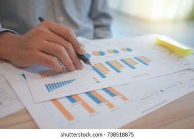 A businessman is analyzing and pointing to the graph of the revenue company at the document.