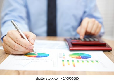 businessman is analyzing report and using calculator