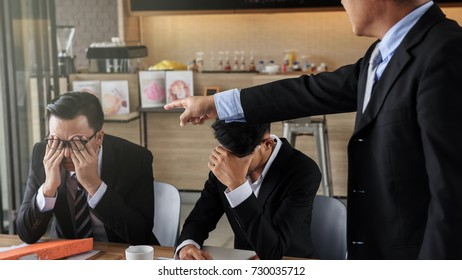 Businessman angry boss manager pointing his finger to working team to complaint for project delay and unsuccessful while both young businessmen raise hands to close or cover their faces.