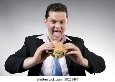 Businessman anxious to eat his hamburger. Studio shot