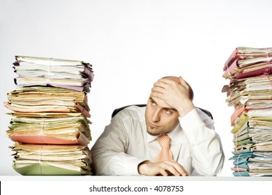 Businessman appears to be overwhelmed by his workload.  Stacks of files are on either side of him.  Isolated on white background.