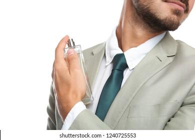 Businessman applying perfume on white background, closeup