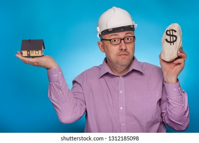 A businessman, architect in a piked shirt and hard hat has a house and a bag of dollars in his hand,  on the blue background.