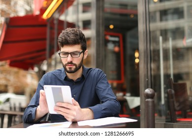 Businessman arguing, discussing project with partner by smartphone and reading papers at cafe table. Handsome man has fleecy dark hair Concept of tariff plan for long conversations and making biz