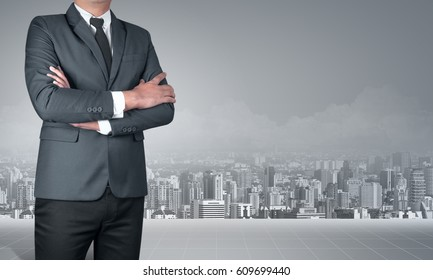 businessman with arms crossed and city concept
