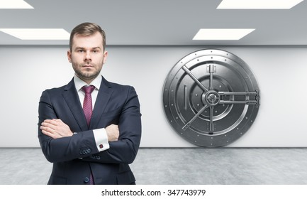 businessman with arms crossed standing in front of a big locked round metal safe in a bank depository,  a concept of security,  front view,