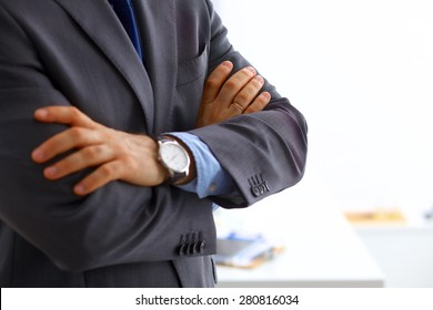 Businessman with arms folded standing in office